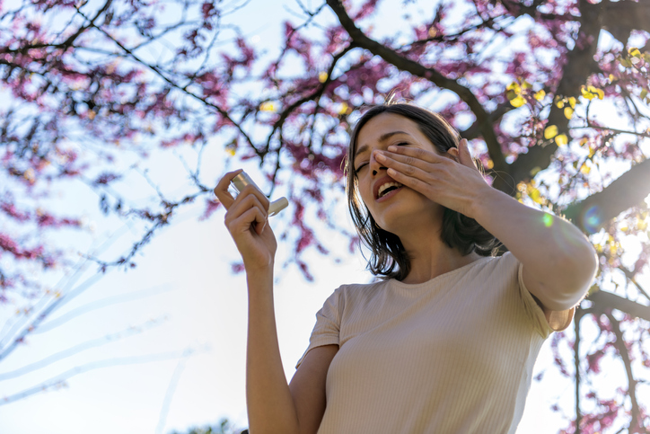 Asthmatic Woman Suffers From Asthma and is Using Inhaler in the Public Park. Chronic Disease Control, Allergy Induced Asthma Remedy and Chronic Pulmonary Disease Concept.