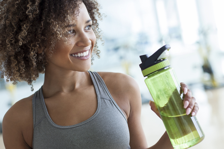 young woman holding a plastic bottle of water at the gym