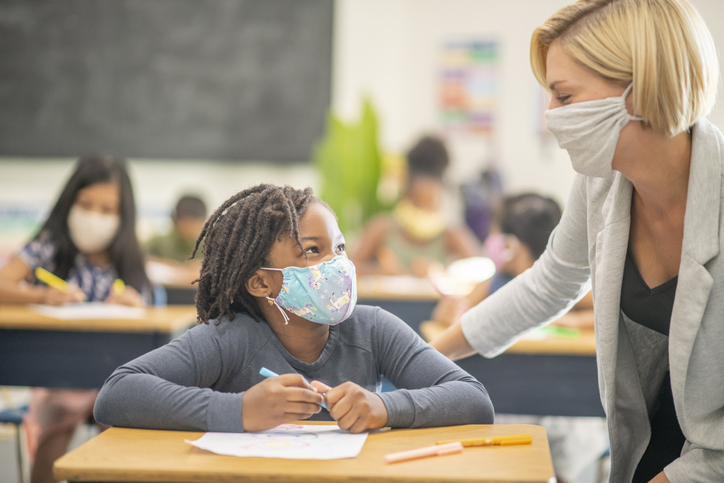 Female student wearing a reusable face mask while sitting at her desk in class.